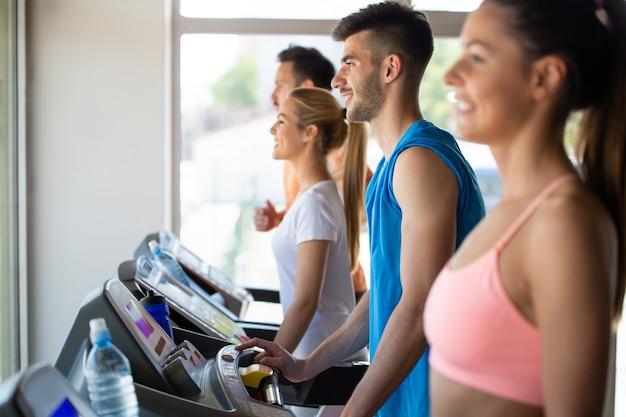 체육관에서 디딜방아에서 달리는 행복한 젊은 사람들의 그룹. 건강, 스포츠 개념