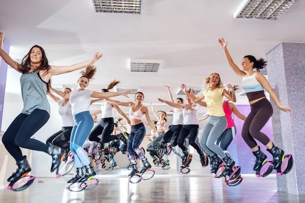 Kangooでジャンプ幸せなフィットの若い女性のグループは、フィットネススタジオで靴をジャンプします。