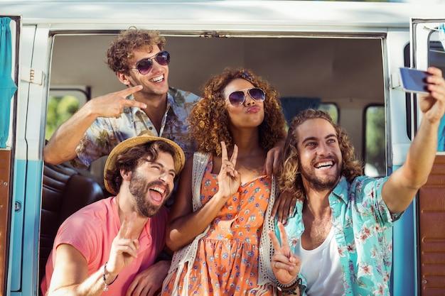 キャンピングカーでselfieを取って幸せな友人のグループ