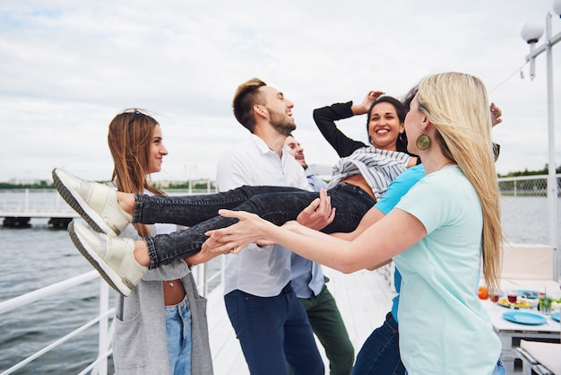 Группа счастливых друзей на пляже, мужчина, бросая счастливую женщину.