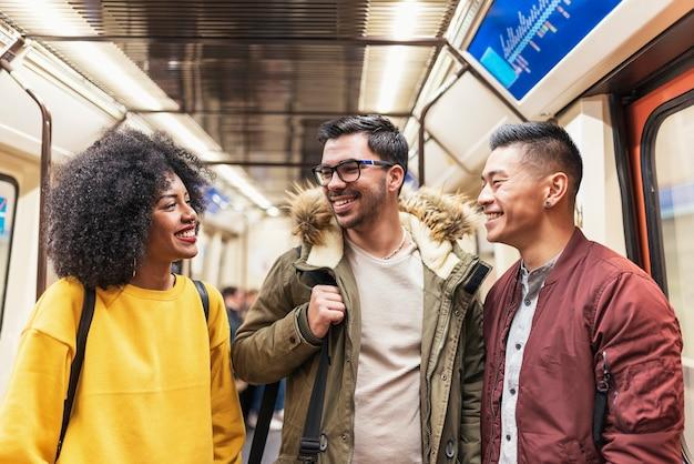 地下鉄でおしゃべりする幸せな友達のグループ。友情の概念。