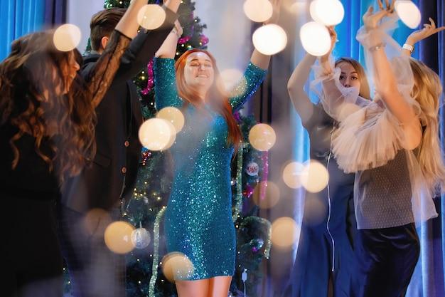 크리스마스 트리 근처에서 춤추는 행복한 친구들. 여성들은 웃고 기뻐합니다. 노이즈 및 그레인, 흐릿한 조명에 대한 빈티지 필터입니다.