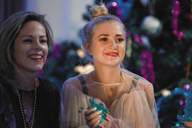 크리스마스 트리 근처에서 춤추는 행복한 친구들. 여성들은 웃고 기뻐합니다.