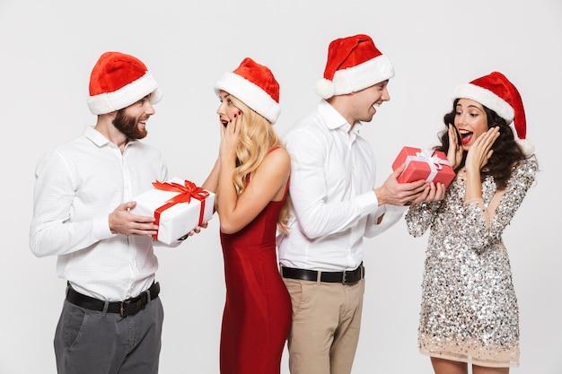 Группа счастливых друзей, одетых в красные шляпы, стоя изолированно на белом, празднует новый год и обменивается подарками