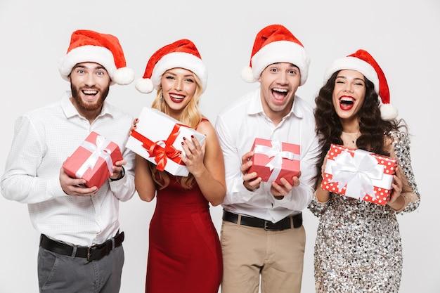 Группа счастливых друзей, одетых в красные шляпы, стоя изолированно над белой, празднует новый год, держа в руках настоящие коробки