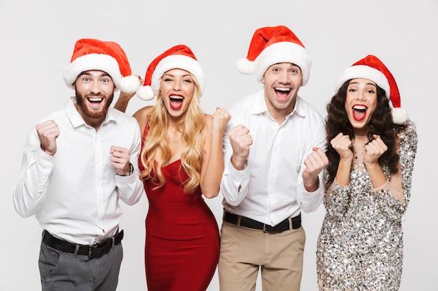 Группа счастливых друзей, одетых в красные шляпы, стоя изолированно над белой, празднует новый год