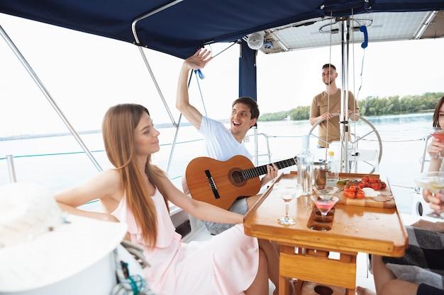 야외 보트 파티에서 보드카 칵테일을 마시는 행복한 친구들의 그룹은 명랑하고 행복합니다. 바다 여행, 청소년, 여름 휴가 개념에서 기타를 치는 젊은이들. 술, 휴가, 휴식.