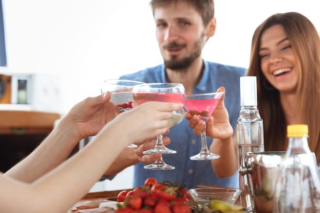 쾌활하고 행복한 야외 보트 파티에서 보드카 칵테일을 마시는 행복한 친구들