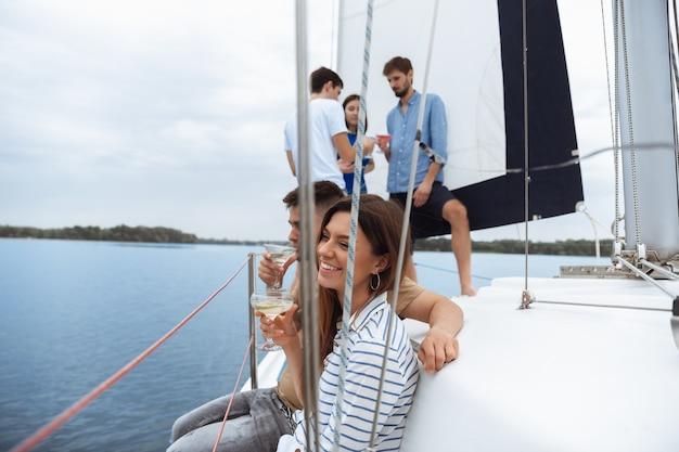 夏の屋外ボートパーティーでウォッカカクテルを飲む幸せな友人のグループ