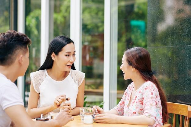 屋外カフェで朝食を食べる幸せな友人のグループ