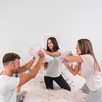 Group of happy friends enjoying pillow fight on bed