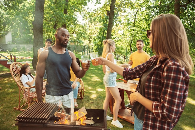 화창한 날에 맥주와 바베큐 파티를 데 행복 친구의 그룹입니다. 숲 사이의 빈터 또는 뒤뜰에서 야외에서 함께 휴식을 취하십시오. 축하하고 휴식을 취하고 웃음. 여름 라이프 스타일, 우정 개념.