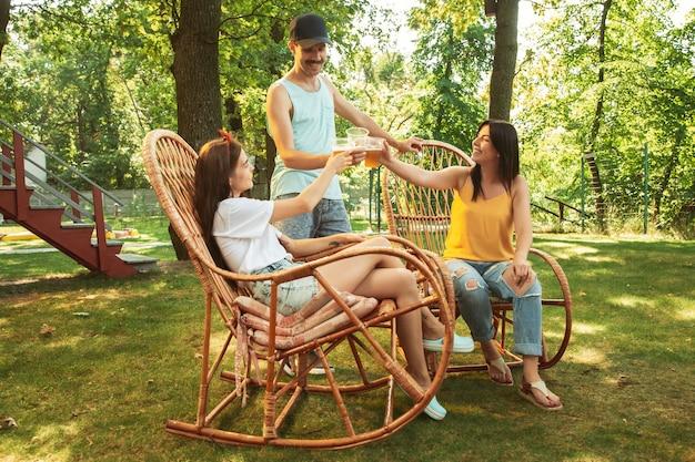 晴れた日にビールとバーベキューパーティーをしている幸せな友人のグループ。森の空き地や裏庭で一緒に屋外で休んでください。祝ってリラックスして、笑って。夏のライフスタイル、友情の概念。