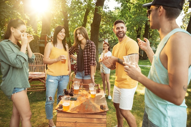 화창한 날에 맥주와 바베큐 파티를 데 행복 친구의 그룹입니다. 숲 사이의 빈터 또는 뒷마당에서 야외에서 함께 휴식