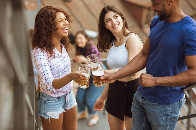 Группа в составе счастливые друзья имея вечеринку пива в летнем дне. отдыхаем вместе на свежем воздухе, празднуем и отдыхаем, смеемся. летний образ жизни, концепция дружбы.