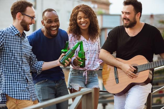夏の日にビールパーティーをしている幸せな友達のグループ