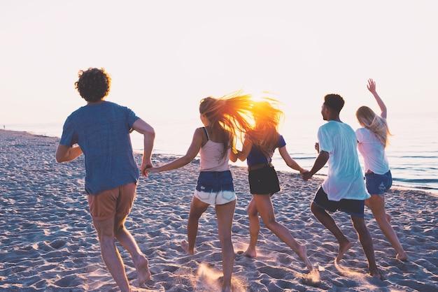 夜明けにオーシャンビーチで楽しんでいる幸せな友達のグループ