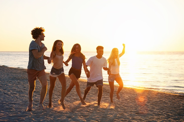 夜明けのオーシャン ビーチで楽しんでいる幸せな友達のグループ
