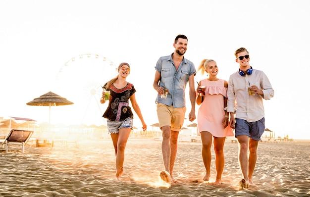 Группа счастливых друзей, весело проводящих время на закате у моря