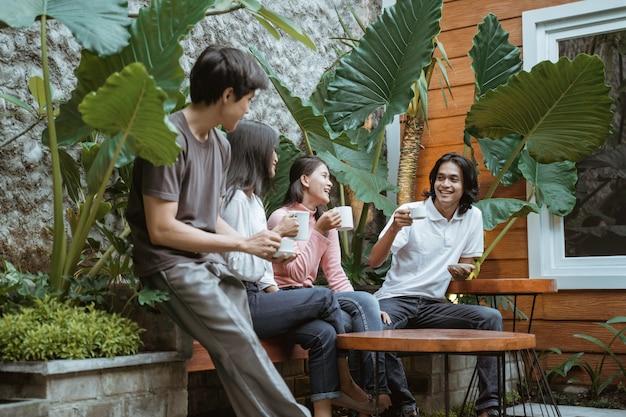Группа счастливых друзей, весело проводящих время в саду, модные молодые люди проводят время вместе