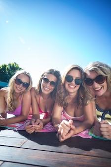 Группа счастливых друзей, лежащих возле бассейна