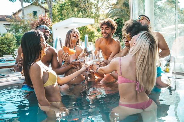 Группа в составе счастливые друзья делая вечеринку у бассейна провозглашать с шампанским. молодые люди смеются, выпивая игристое вино в роскошном курорте.