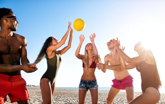 ビーチでビーチバレーで遊んでいる幸せな友達のグループ