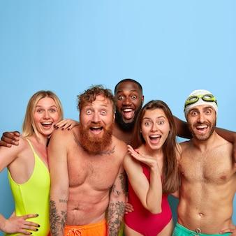 해변에서 포즈를 취하는 행복 한 친구의 그룹