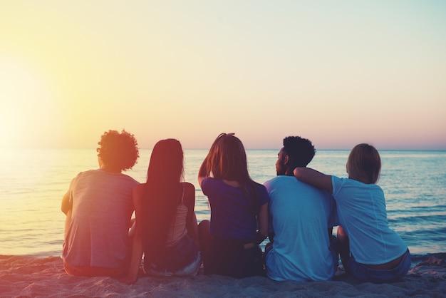 日没時にビーチでリラックスして幸せな友達のグループ