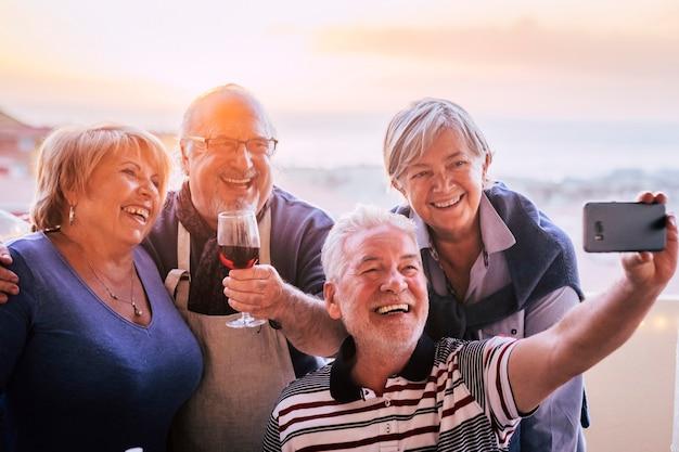 幸せな友達のグループ高齢者は、スマートフォンで自分撮りをする社会的接触と一緒に楽しんでいます-屋外で成熟したお祝い-引退したライフスタイルと男性女性は友情で笑顔で笑います Premium写真