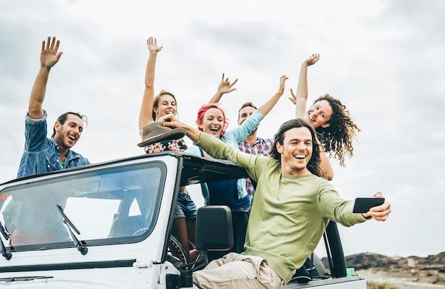 ジープ車にモバイルスマートフォンでselfieを取って幸せな友人のグループ