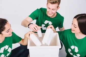 Group of happy friends throwing bottles in white dustbin