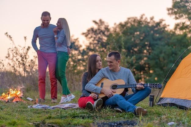 Группа счастливых друзей с гитарой, с удовольствием на открытом воздухе, возле костра и туристической палатки. кемпинг веселая счастливая семья