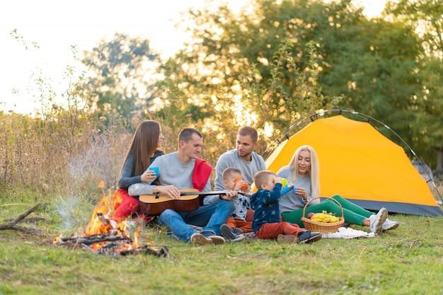 テントとキャンプでギターを弾く飲み物と幸せな友達のグループ