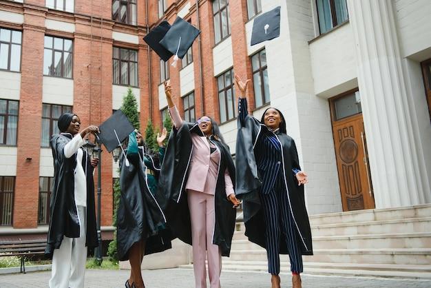 Группа счастливых выпускников, бросающих выпускные шляпы в воздух, празднуя