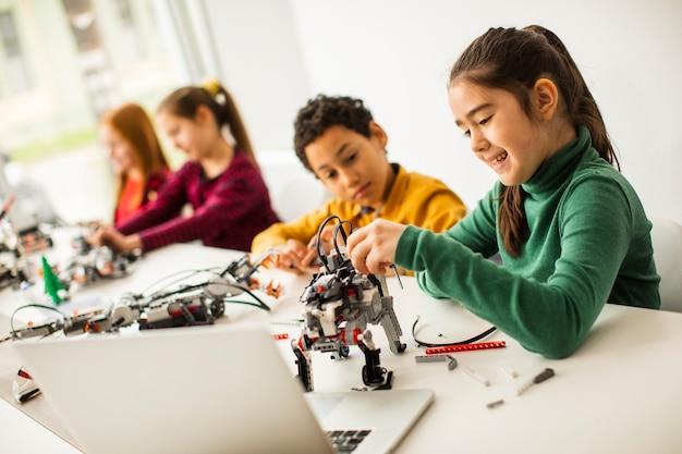 ロボット工学の教室で電気おもちゃとロボットをプログラミングする幸せな子供たちのグループ