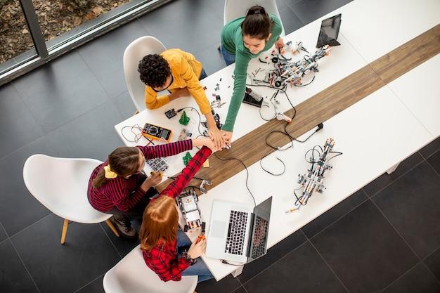 Группа счастливых детей, программирующих электрические игрушки и роботов в классе робототехники