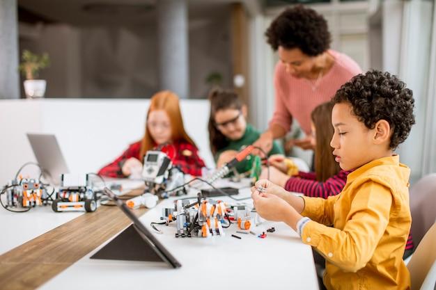ロボット工学の教室でラップトッププログラミング電気おもちゃとロボットを持つアフリカ系アメリカ人の女性科学教師と幸せな子供たちのグループ