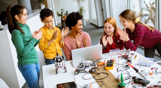 로봇 교실에서 전기 장난감과 로봇을 프로그래밍하는 노트북과 함께 아프리카 계 미국인 여성 과학 교사와 함께 행복한 아이들의 그룹