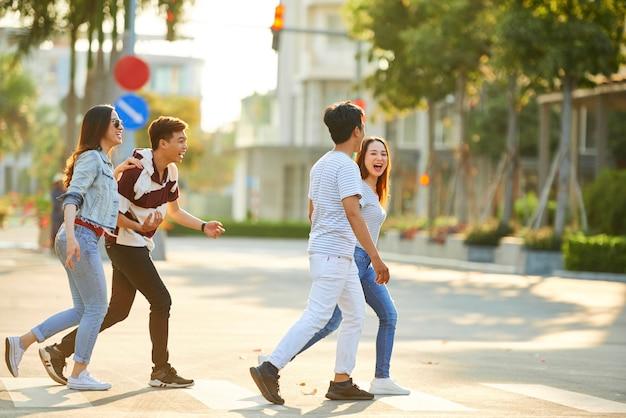 晴れた夏の日に道路を横断する幸せな笑う若いベトナム人のグループ