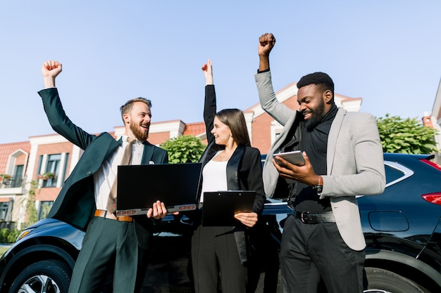 ノートパソコンやタブレットを操作して成功を祝う幸せな多民族のビジネス人々のグループは、車の前に屋外に立っている間、拳を上げて興奮させます。ビジネスグループの概念