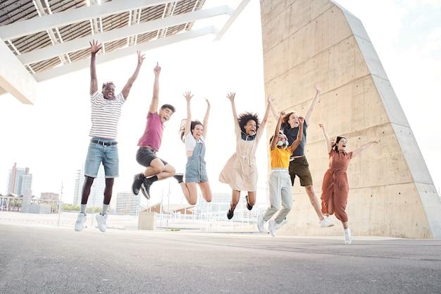 Группа счастливых многонациональных друзей веселится, молодые студенты прыгают за пределы университета
