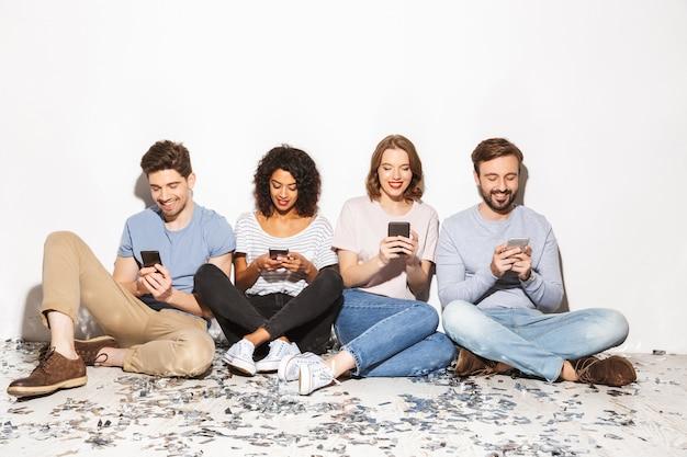 Группа счастливых многорасовых людей, сидящих на полу