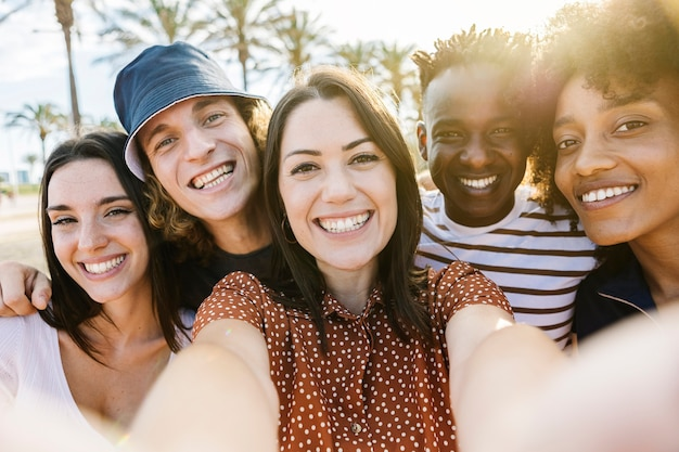 Группа счастливых многорасовых людей, делающих селфи с мобильным телефоном на открытом воздухе с обратным солнечным светом