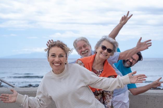 Группа счастливых людей, весело проводящих время вместе на море, облачное небо. семья из нескольких поколений, демонстрирующая позитив и свободу