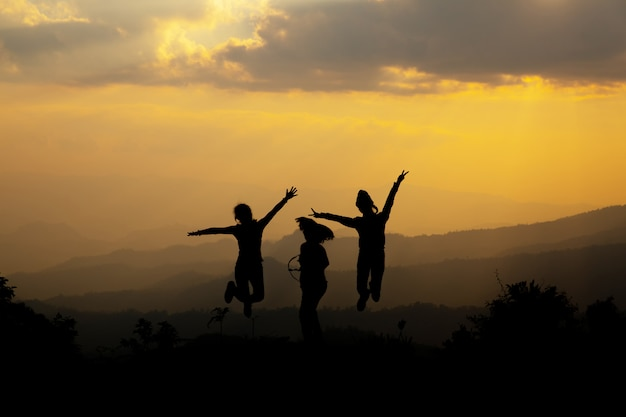 夕暮れ時の山でジャンプ幸せな人々のグループ