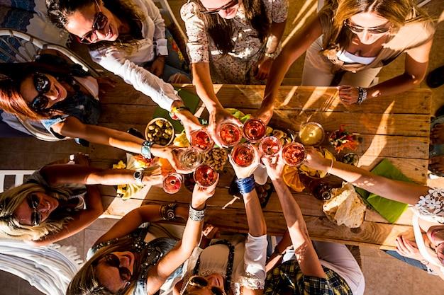 행복한 사람들의 그룹은 축하 파티 동안 모두 함께 재미를 혼합 연령 세대의 여성-악마의 세로보기와 레드 와인과 음식으로 가득한 테이블 토스트