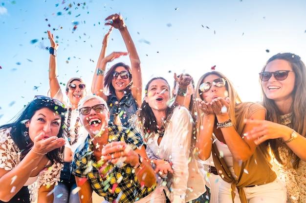 행복 한 사람들의 그룹 혼합 연령 세대 여성 축 하 파티 동안 모두 함께 재미-악마 불고의보기. 색종이 조각과 우정에서 많이 웃어