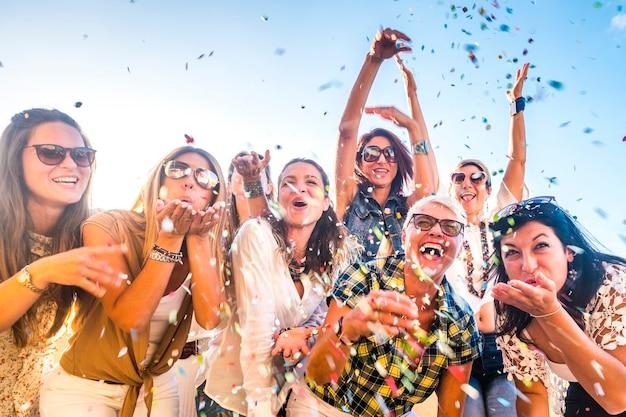 幸せな人々のグループは、お祝いパーティーの間に一緒に楽しんでいる年齢世代の女性を混ぜ合わせました-悪鬼が吹いているの眺め。色付きの紙吹雪と友情でたくさん笑う