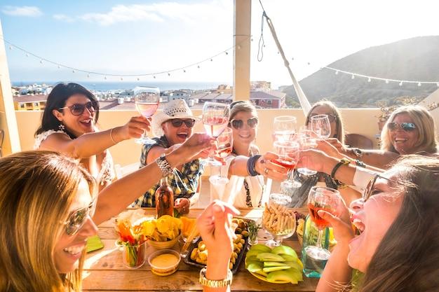 행복한 사람들의 그룹은 축하 파티 동안 모두 함께 재미를 혼합 연령 세대의 여성-음식으로 가득 찬 레드 와인과 테이블을 부딪 치고 토스트하는 악마의보기